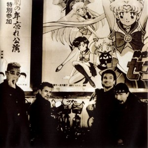 U2 in front of a Sailor Moon R The Movie poster