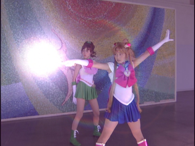 Live Action Pretty Guardian Sailor Moon Act 7 - Sailor Jupiter and Sailor Moon in front of a mural