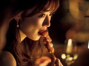 Rika Izumi eats a piece of bacon